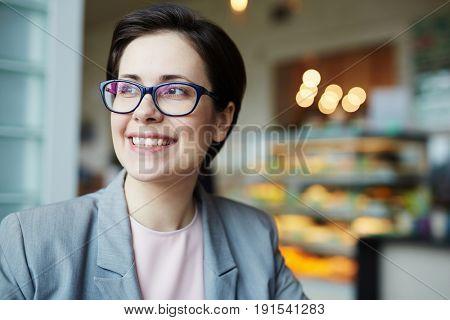 Portrait of smiling contemporary businesswoman looking away to window enjoying coffee break in cafe