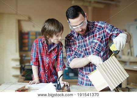 Little boy and his father measuring height of starling-house in workshop