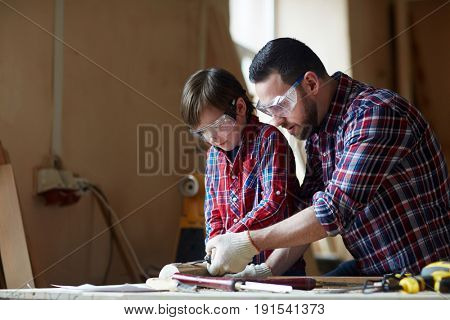 Little trainee learning to woodcarve while his father teaching him