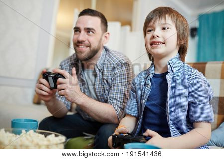Happy boy and his father playing video game at leisure