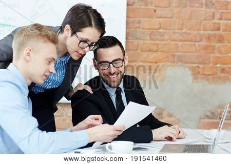 Contemporary traders reading papers in office