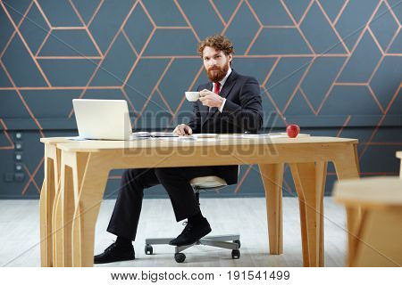 Confident leader with cup of tea sitting by table in front of laptop