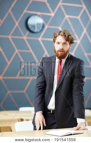 Serious employer in elegant formalwear standing by workplace