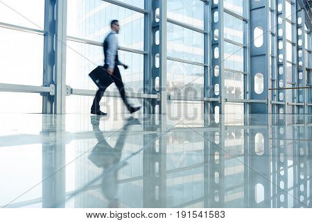 Blurred shape of business person walking in hall of modern glass building, going to work