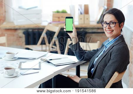 Happy businesswoman sitting by workplace and showing touchscreen of smartphone