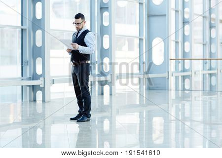 Portrait of contemporary successful businessman reading documents in hall of modern office building, copy space
