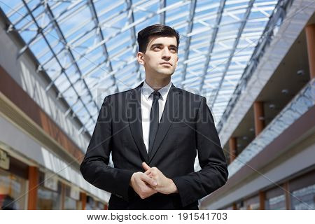 Low angle portrait of successful businessman standing confidently looking away under glass ceiling in modern office building