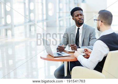 Portrait of successful African-American businessman looking skeptically at his colleague during work meeting at coffee break