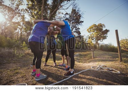 Portrait of womens group forming huddles in the boot camp