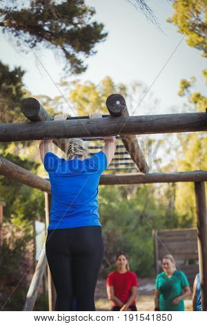 Rear view of woman climbing monkey bars during obstacle course training in the boot camp