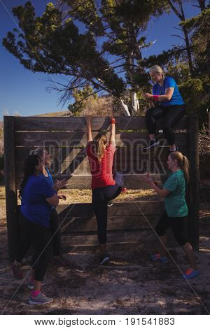Woman being cheered by her teammates to climb a wooden wall during obstacle course training at boot camp