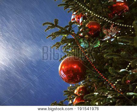 red ball on christmas tree on snowy dark sky background