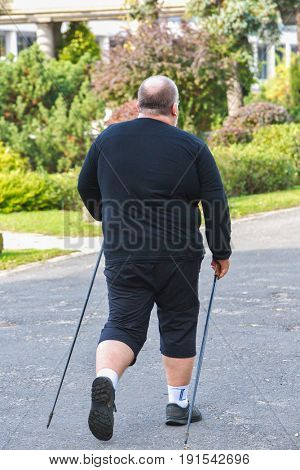Big man Nordic Walking in beautiful public park