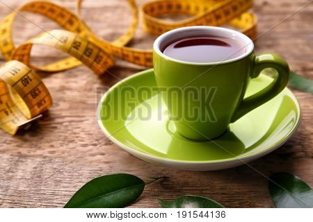 Cup of tea and measuring tape on wooden background