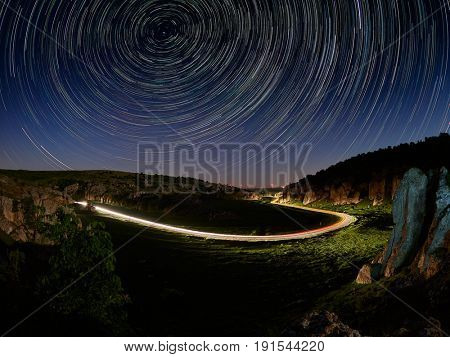 Night sky with star trails, night road illuminated by car's light trails - Cheile Dobrogei, Romania