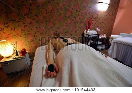 Stone massage. Beautiful woman getting spa hot stones massage in spa salon