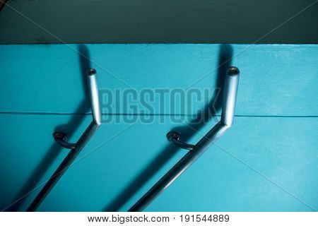 Parallel stainless steel handrails on blue wall