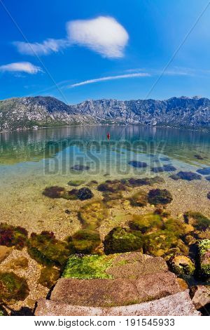 Stones beach with sea and mountain views. fisheye look. Montenegro