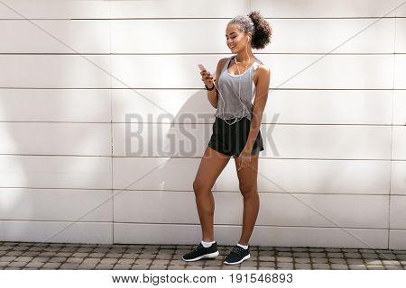 Smiling woman listening to music, taking short break during workout