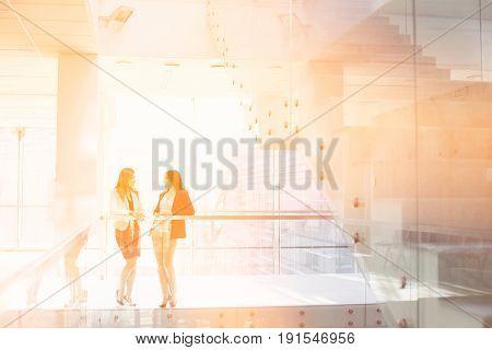 Businesswomen conversing against railing in office