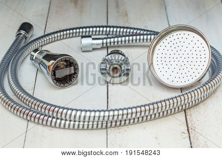 Three different shower sprinklers and shower bowel on wooden shelves