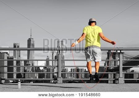 Morning exercises with skipping rope on the background of the city