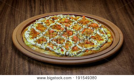 Delicious brazilian pizza with cheese, shrimp with catupiry isolated over a wooden background