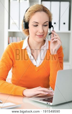 Young beautiful business woman in headset or call operator communicates by laptop computer. Orange sweater is uniform of a girl.