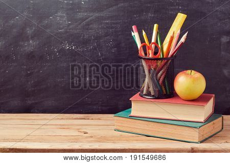 Back to school background with books pencils and apple over chalkboard