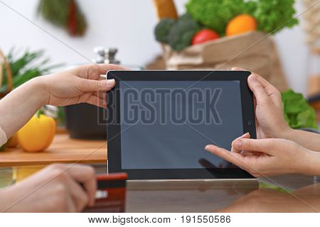 Human hands pointing into touch pad with copy space area. Two woman making menu in the kitchen, closeup. Cooking and friendship concept