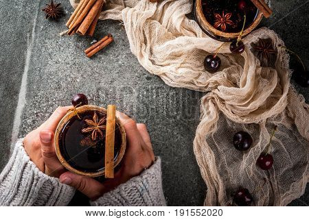 Autumn and winter drinks. Hot cherry sangria with cinnamon anise wine and spices. On a stone dark and wooden background. Girl is holding glass with drink. Female hands in sweater. Top view copy space