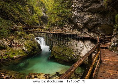 Wooden walkway through Vintgar Gorge canyon with a bridge over the emerald water of the stream in the mountains near Bled in Slovenia.