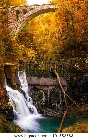 Waterfall at the end of Vintgar Gorge canyon under an old railway bridge with trees and other vegetation along the river in autumn colors near Bled in Slovenia.