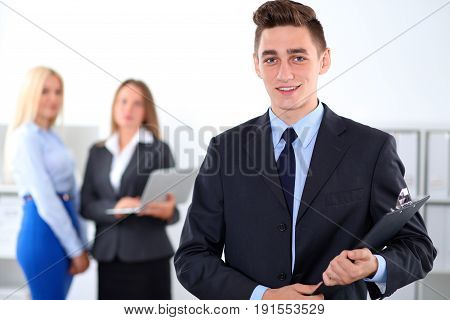 Cheerful business man in office with colleagues in the background, start-up team.