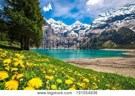 Amazing tourquise Oeschinnensee with waterfalls wooden chalet and Swiss Alps Berner Oberland Switzerland.