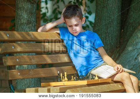 boy with a book in his hand plays chess. Young chess player on a chessboard. kid with a chess textbook thinks over a chess combination