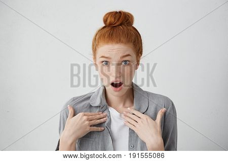 Is It Me? Shocked Red-haired Teenage Girl With Freckles And Blue Eyes Pointing At Herself With Hands