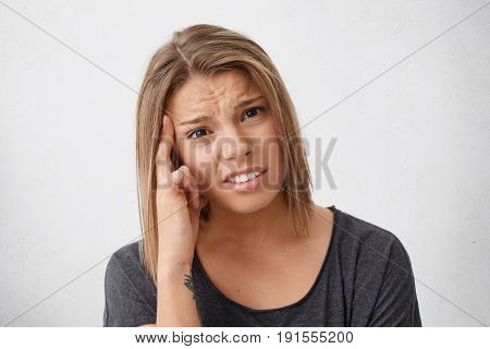 Close-up Portrait Of Cute Woman With Brown Eyes And Srtylish Hairdo Holding Her Finger On Temple Bei