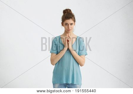 Hopeful Begging Woman In Casual Clothes With Hair Bun Keeping Her Palms Together Asking For Somethin