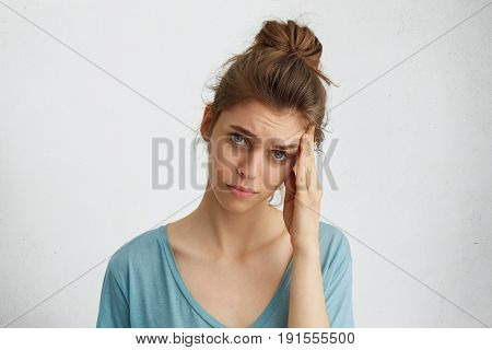 Depressing Doleful Woman With Hair Knot, Blue Exhausted Eyes Touching Her Head Having Discontented E