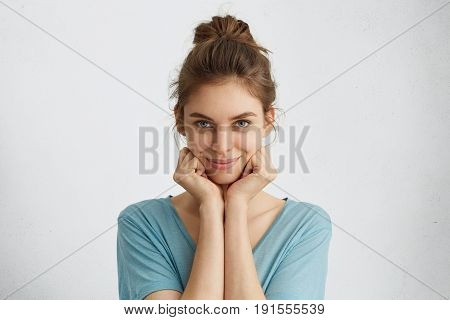 Horizontal Portrait Of Cute Young Woman With Blue Eyes And Gentle Smile Holding Hands Under Chin Loo