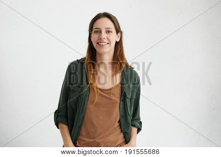 Pleased Pretty Woman With Dyed Hair, Dark Eyes And Healthy Skin Dressed In Brown T-shirt, Green Jack