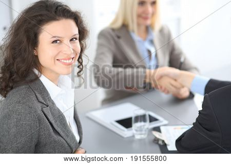 A group of business people at a meeting on the background of office. Focus on a beautiful brunette.