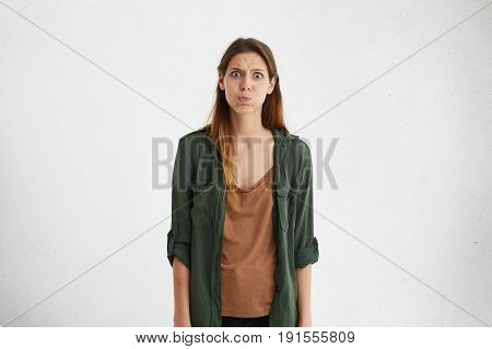 Upset Offended Brunette Woman Looking With Big Eyes In Camera Blowing Cheeks Being Annoyed After Qua