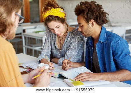 Interracial Group Of Students Sitting At Desk Having Concentrated Look In Book Doing Tests Marking R