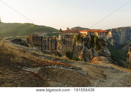 Meteora monasteries. Beautiful evening view on the Holy Monastery of Varlaam placed on the edge of high rock, Roussanou Monastery on background. Kastraki, Greece