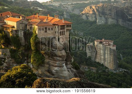 Meteora monasteries. Beautiful morning view on the Holy Monastery of Varlaam placed on the edge of high rock, Roussanou Monastery on background. Kastraki, Greece
