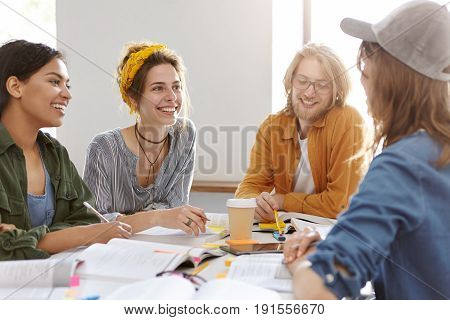 Horizontal Portrait Of Multi-ethnic Encouraged Students Surrounded With Books Having Talk Working To