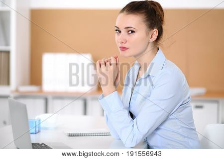 Young business woman working on laptop in office. Successful business concept