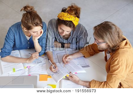 Two Pupils Working With Their Tutor Doing Home Assigment Sitting At White Table. Three College Stude